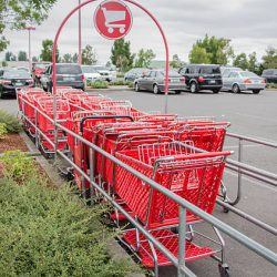 Eugene, Oregon, USA - July 20, 2014: Cart coral full of red carts at a local Target Department Store with a parkling lot full of vehicles.